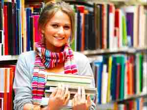 Pretty charming woman holding books in library